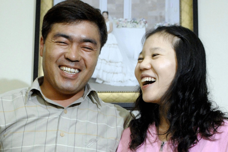 <p>Kim Choong-Hwan (left), a 40-year-old South Korean truck driver, poses with his Vietnamese wife Ngo Ngoc Quy Hong, 21, by their wedding photo after an interview at their apartment in Osan, south of Seoul, May 3, 2007. A growing army of South Korean bachelors are turning to China, Vietnam, the Philippines, Mongolia, Thailand, Russia, Uzbekistan and other foreign countries for brides.</p>
