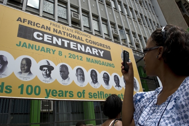 <p>A woman takes a picture of a poster in Bloemfontein on January 5, 2012 to celebrate the 100th anniversary of South Africa's ruling African National Congress (ANC) party.</p>