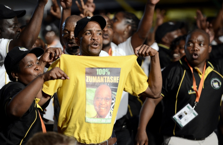 <p>A supporter of South African President Jacob Zuma holds a t-shirt baring his portrait, among African National Congress (ANC) delegates attending the opening ceremony of the 53rd National Conference of the African National Congress (ANC) on December 16, 2012, in Bloemfontein.</p>