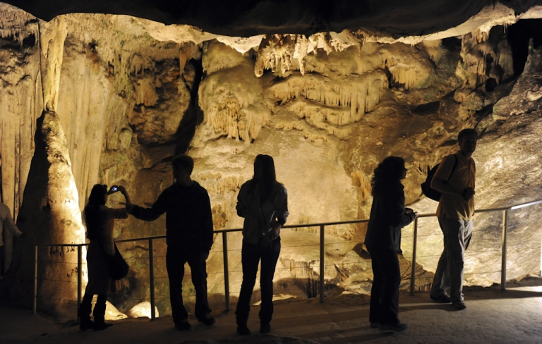 <p>Visitors look at stalactites at the Cango Caves in Oudtshoorn, north of the South African city of George. Researchers have discovered what they believe may be the remnants of an ancient art studio, at Blombos Cave on South Africa's southern Cape Coast.</p>