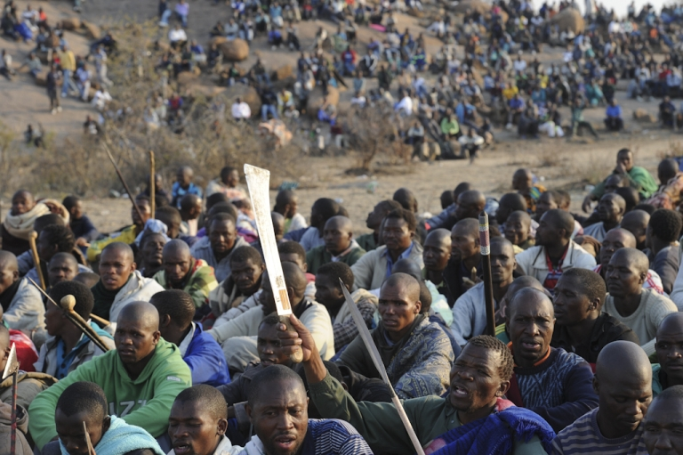 <p>Striking mineworkers armed with machetes are monitered by a large number of police as they stage a sit-in on a hill near the Marikana mine in Rustenburg, 62 miles northwest of Johannesburg on August 15, 2012, where they are demading a wage increase. Ten people were killed in clashes at the platinum mine, which is run by leading producer Lonmin, between rival unions, the leading and decades-old National Union of Mineworkers (NUM) and the smaller Association of Mineworkers and Construction Union (AMCU).</p>