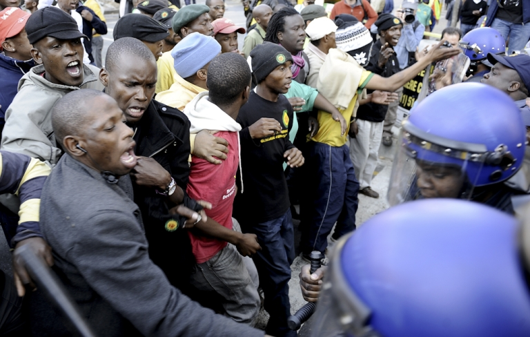 <p>Supporters of controversial African National Congress (ANC) youth leader Julius Malema face Police on August 30, 2011 in Johannesburg ahead of his disciplinary hearing. Hundreds of Malema supporters threw stones and bottles at police while burning the ruling party's flag and T-shirts bearing the face of President Jacob Zuma.The 30-year-old firebrand leader is facing charges of 'bringing the ANC into disrepute' and 'sowing divisions' in the ruling party. Malema, who is charged along with five other youth league officials, could be expelled from the ANC at the closed-door hearing.</p>