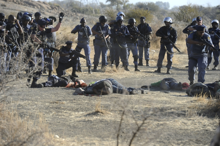 <p>Police surround fallen miners after they opened fire during clashes at the Lonmin Marikana platinum mine near Rustenburg, South Africa, on August 16, 2012. Hundreds of workers armed with machetes, sticks and metal rods had gathered on a hillside near the mine, defying police orders to disperse. Several people were lying on the ground, some bleeding from wounds, after the crowd fled, according to an AFP reporter. Police say at least 30 people were killed.</p>