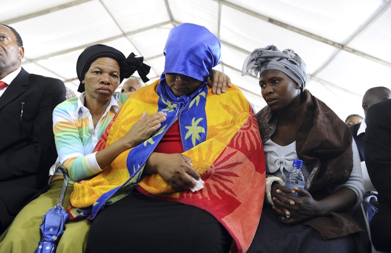 <p>A woman is comforted during a memorial service for the 44 people killed in a wildcat strike at Lonmin's Marikana mine on August 23, 2012 in Marikana. Lonmin and nearby Impala Platinum closed for the day as workers prepared for memorials, including the main national service at Marikana where police gunned down 34 miners a week ago after deadly clashes had already claimed 10 people. The service at Lonmin will be the focal point during a day of mourning that will stretch across the country, as many of the victims were migrant workers whose bodies have already returned to their home villages.</p>