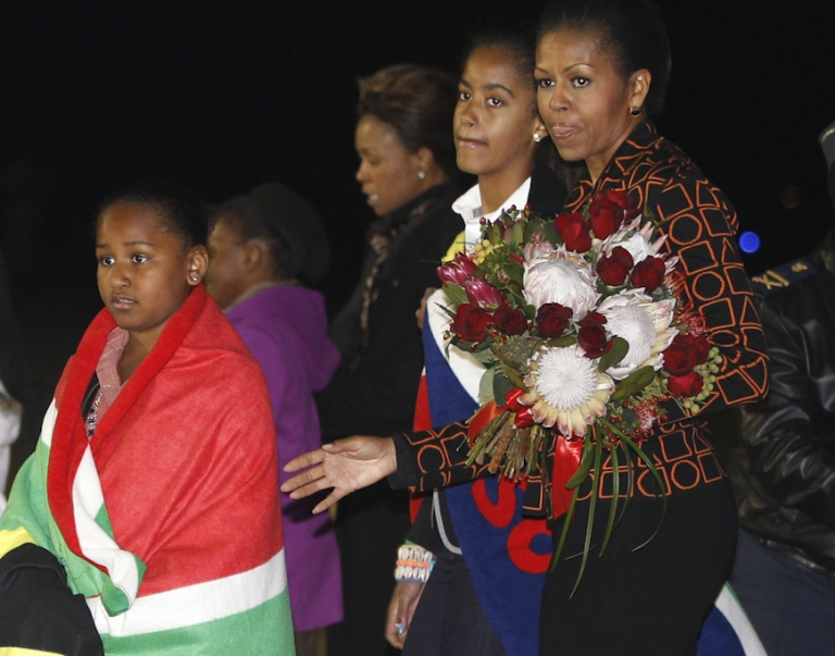 <p>US first lady Michelle Obama holds a bouquet of flowers as daughters Malia and Sasha, are draped in blankets given to them upon landing in Pretoria en route to Johannesburg, South Africa, as they begin their week long trip to Africa on June 20, 2011.</p>