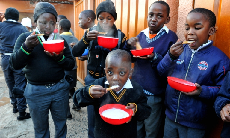 <p>In this picture taken on May 17, 2012 some of the 100 children who have lost parents to AIDS in Alexandra township in the north of Johannesburg enjoy a bowl of piping hot corn meal porridge given to them by Mama Portia.</p>