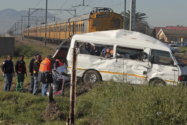 <p>Rescuers stand at the scene of a fatal crash between a minibus taxi, carrying children to school, and a commuter train on August 25, 2010 on the outskirt of Cape Town. Road accident deaths are twice as high in South Africa as the global average.</p>