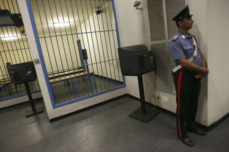 <p>A member of the Italian Carbiniere stands by an empty cell in the Pagliarelli prison on June 29, 2010.</p>