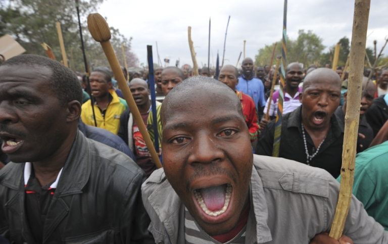 <p>Thousands of striking workers singing and carrying sticks march on a South African mine in Marikana on Sepember 5, 2012, as police were accused of shooting miners in cold blood during a crackdown that killed 34. Armoured police trucks and two police helicopters kept watch as around 3,000 miners arrived at the entrance of a shaft owned by the world's number three platinum producer Lomin where a deadly strike is now in its fourth week.</p>