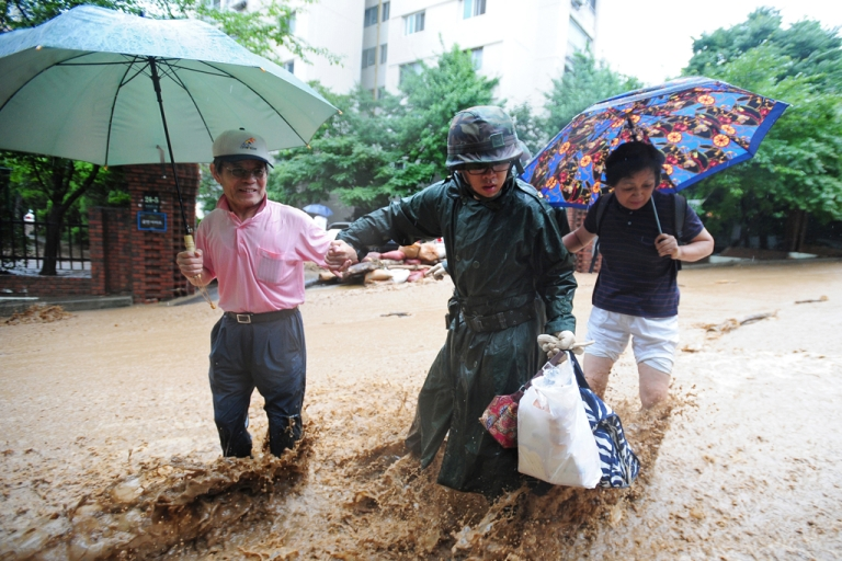 <p>A South Korean soldier (C) escorts isolated residents through floodwaters and mud after a flood caused by heavy rains hit the area around an apartment complex in Seoul on July 28, 2011.</p>