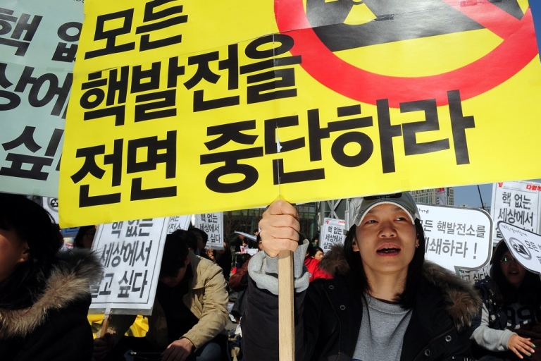 <p>A South Korean environmental activist holds up a placard that reads 'stop the nuclear power' during an anti-nuclear rally in Seoul on March 26, 2011.</p>