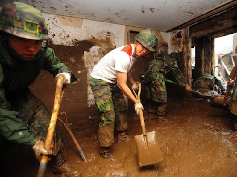 <p>South Korean soldiers remove tons of mud from the inside of a building after a flood caused by heavy rains hit the area around an apartment complex in Seoul on July 28, 2011. Tens of thousands of South Korean troops joined a massive clean-up on July 28 after record-breaking rainfall killed at least 39 people, flooded hundreds of homes and turned main roads into muddy rivers.</p>