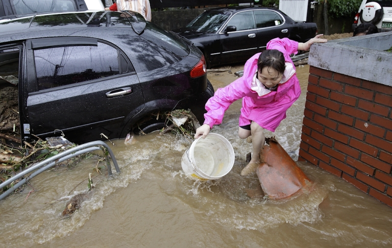 <p>A woman steps across floodwater after a torrential rain storm hit the capital city on July 27, 2011 in Seoul, South Korea. South Korea issued a national crisis warning on as torrential rain caused flooding in parts of the country, killing over 35 with at least ten missing.</p>
