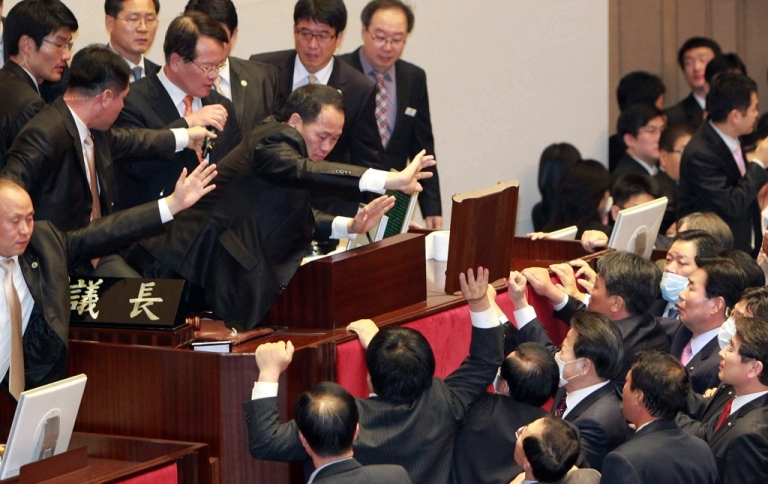 <p>South Korea's opposition party lawmakers protest at the chairman's seat inside the National Assembly in Seoul, to try to stop the ruling Grand National Party's move to ratify a bill on a free trade agreement with the United States on November 22, 2011.</p>