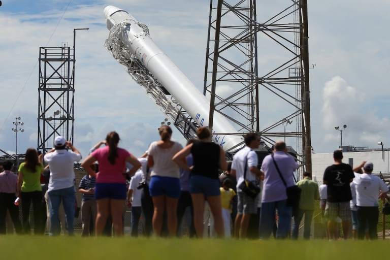 <p>CAPE CANAVERAL, FL - OCTOBER 07: People watch as a SpaceX Falcon 9 rocket attached to the cargo-only capsule called Dragon is raised into launch position as it is prepared for a scheduled evening launch on October 7, 2012 in Cape Canaveral, Florida. The rocket will bring cargo to the International Space Station that consists of clothing, equipment and science experiments.</p>
