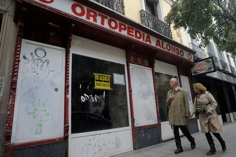 <p>A couple walk past a closed down orthopedic shop on November 10, 2011 in Madrid.</p>
