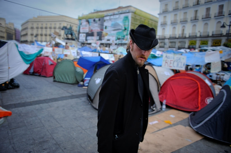 <p>A man stands among tents as protesters camp at the Puerta del Sol square in Madrid on May 27, 2011.</p>