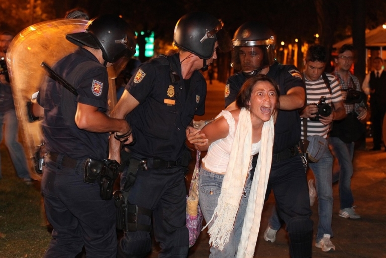 <p>Spanish riot policemen arrest a woman on August 4, 2011 as they charged hundreds of