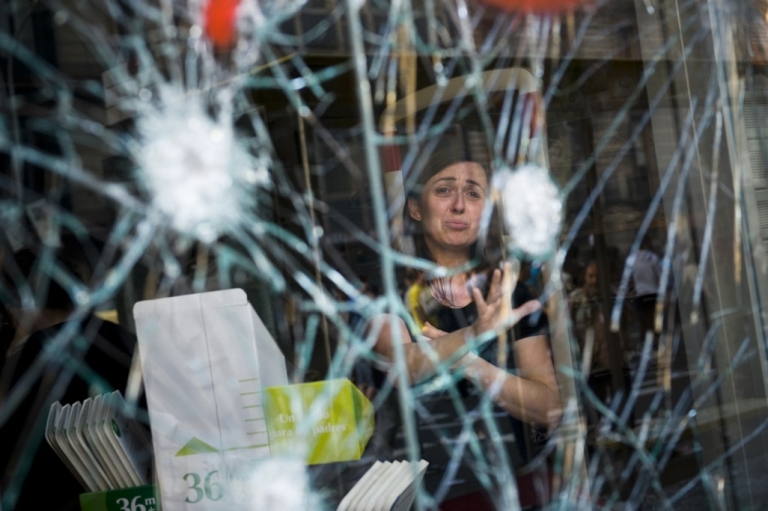 <p>A woman cries behind the smashed window of her shop during heavy clashes with riot police during a 24-hour strike on March 29, 2012 in Barcelona, Spain.</p>