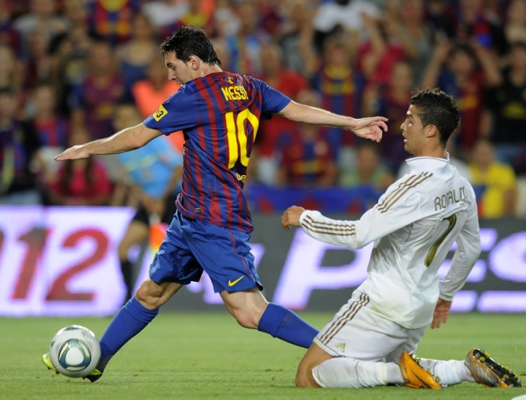 <p>Barcelona's Argentinian forward Lionel Messi (L) scores a goal as he vies with Real Madrid's Portuguese forward Cristiano Ronaldo during the second leg of the Spanish Supercup football match FC Barcelona vs Real Madrid CF on August 17, 2011 at the Camp Nou stadium in Barcelona.</p>