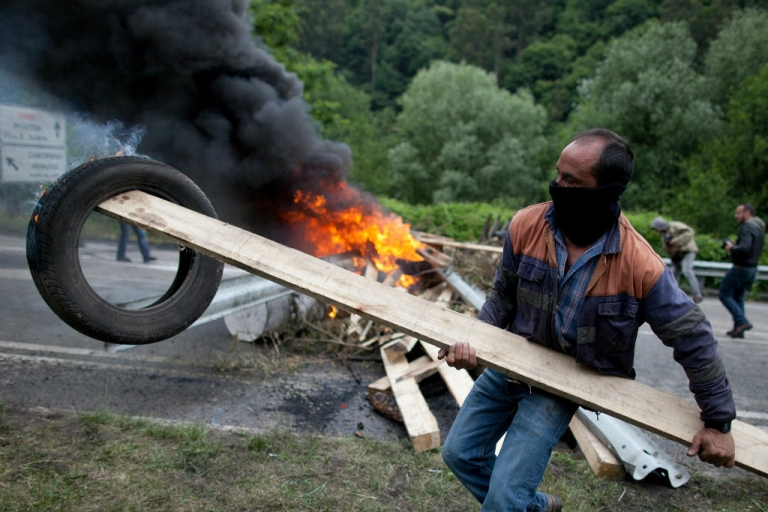 <p>A Spanish miner holds a burning tire next to a barricade near Santiago mine.</p>