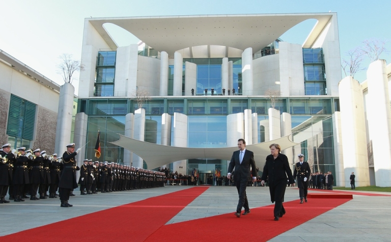 <p>German Chancellor Angela Merkel and Spanish Prime Minister Mariano Rajoy review an honor guard upon Rajoy's arrival at the Chancellery on January 26, 2012 in Berlin, Germany. On February 3, Rajoy approved sweeping new regulations aimed at strengthening Spain's crisis-weakened financial sector.</p>