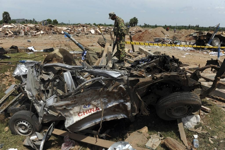 <p>A Sri Lankan policeman looks at the wreckage of a vehicle in the village of Karadiyanaru near Batticaloa , a day after an accidental explosion where 25 people were killed in the first major explosion since the end of a decades-long civil war.</p>