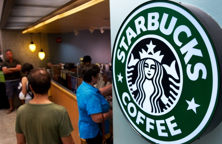 <p>Customers queue for coffee at a Starbucks inside the Dulles International Airport complex on August 30, 2011 in Dulles, Virginia, near Washington, DC.</p>