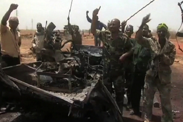 <p>An image grab taken from footage obtained by AFP shows Sudanese troops celebrating next to a burned military vehicle on March 29, 2012, one day after recapturing Sudan's southern oil center of Heglig following fighting with South Sudanese forces along the border. Southern troops have once again seized the Heglig oilfields, parts of which are claimed by both countries.</p>