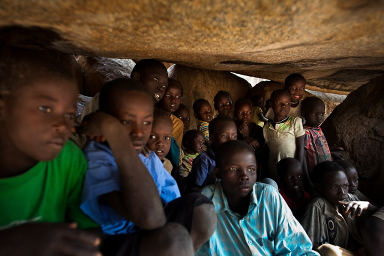 <p>Nuba children take shelter in caves as a Sudan Armed Forces Antonov bomber passes overhead on July 13, 2011.</p>