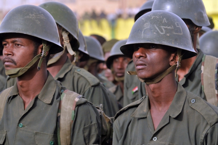 <p>Sudanese soldiers stand to attention during President Omar al-Bashir's visit to the Popular Defence Forces in Khartoum on March 3, 2012.</p>