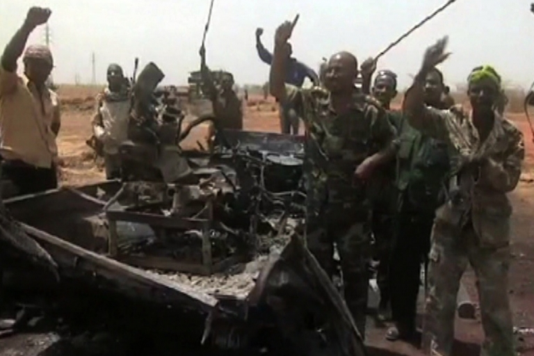 <p>An image grab taken from footage obtained by AFP shows Sudanese troops celebrating next to a burned military vehicle on March 29, 2012, one day after recapturing Sudan's southern oil center of Heglig following fighting with South Sudanese forces along the border. Southern troops had taken the Heglig oil field, parts of which are claimed by both countries, but Sudanese forces later retook the field. Both sides vowed to step back from the brink of all out war after three days of border violence including air strikes and tank battles.</p>
