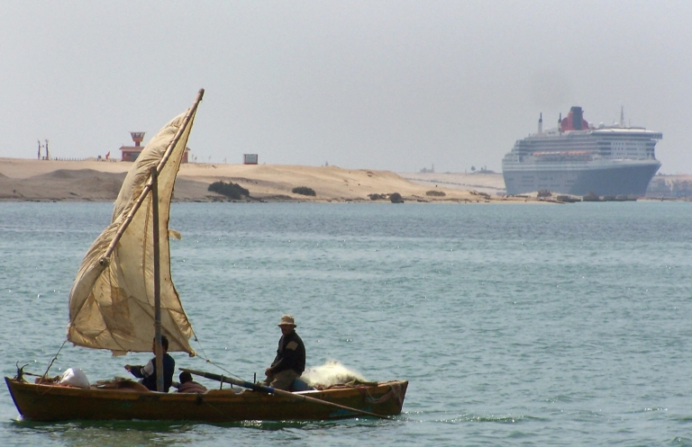 <p>A traditional fishing boat navigates off the Egyptian port town of Ismailia, 80 miles northeast of Cairo, on March 28, 2009, as the luxury ocean liner Queen Mary II (R) transits northbound through the Suez Canal on its way to the Mediterranean Sea.</p>