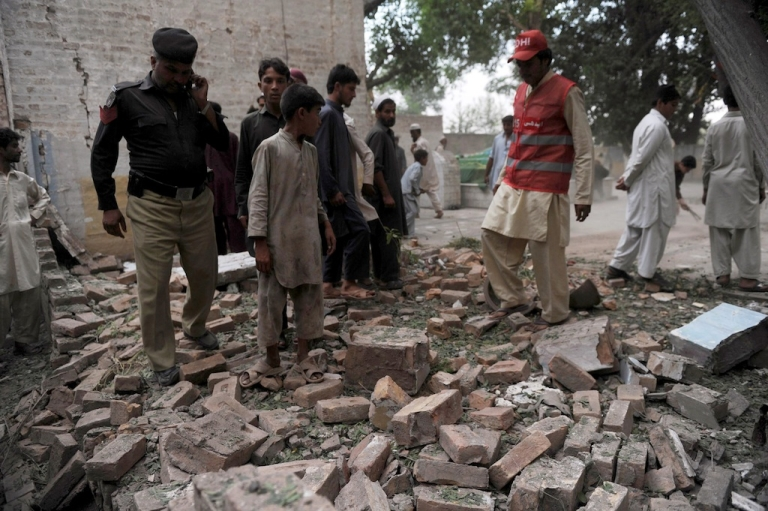 <p>Pakistani police officials inspect a damaged Sufi Shrine after a bomb explosion in Peshawar on June 21, 2012.</p>