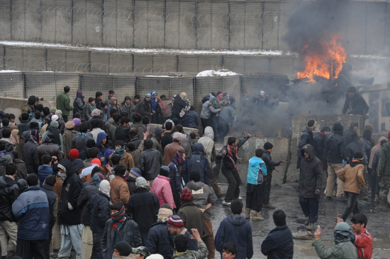 <p>Afghan youth throw stones toward US soldiers standing at the gate of Bagram airbase during a protest against Koran desecration on February 21, 2012 at Bagram about 40 miles north of Kabul. A suicide bomb attack on the NATO base on March 5, 2012 has left two civilians dead.</p>