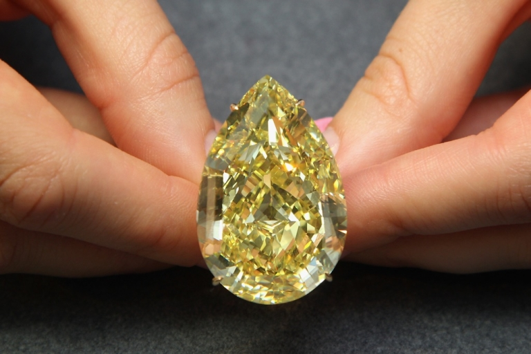 <p>A Sotheby's employee holds a 110.3 carat sun-drop diamond on October 24, 2011 in London, England.</p>