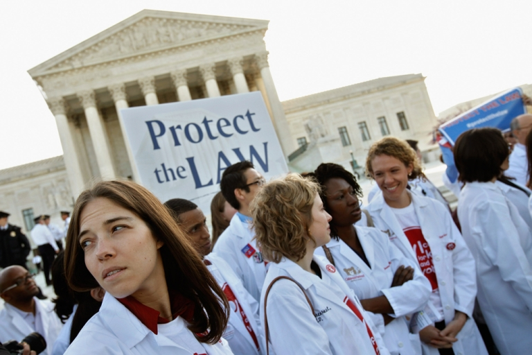 <p>Medical students and professionals participate in a news conference in support of the Patient Protection and Affordable Care Act outside the U.S. Supreme Court Building on March 26, 2012 in Washington, DC. Today the high court, which has set aside six hours over three days, will hear arguments over the constitutionality of the act.</p>