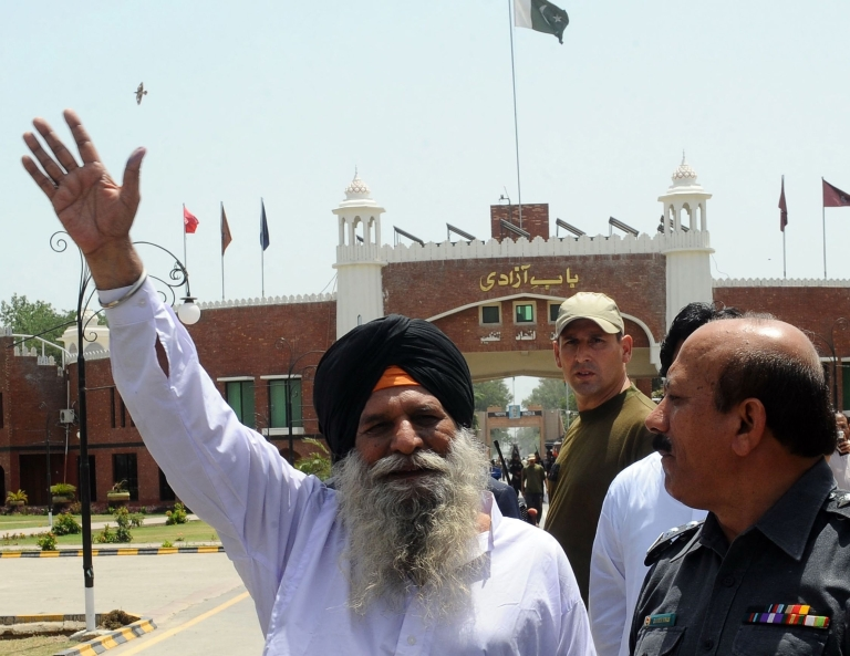 <p>Released Indian prisoner Surjeet Singh, escorted by Pakistani security officials, waves before leaving Pakistan for India at the Wagah border on June 28, 2012.</p>