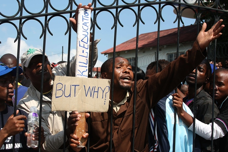 <p>University of Swaziland students locked inside the campus ask police officers to let them out during a protest in Mbabane on November 3, 2011. Hundreds of Swazi students gathered outside state offices in the capital, Mbabane, to demand that the cash-strapped government pay their three-month overdue meal allowances. Armed police locked the crowd of around 300 students inside the University of Swaziland for half an hour before letting them march down a back street.</p>