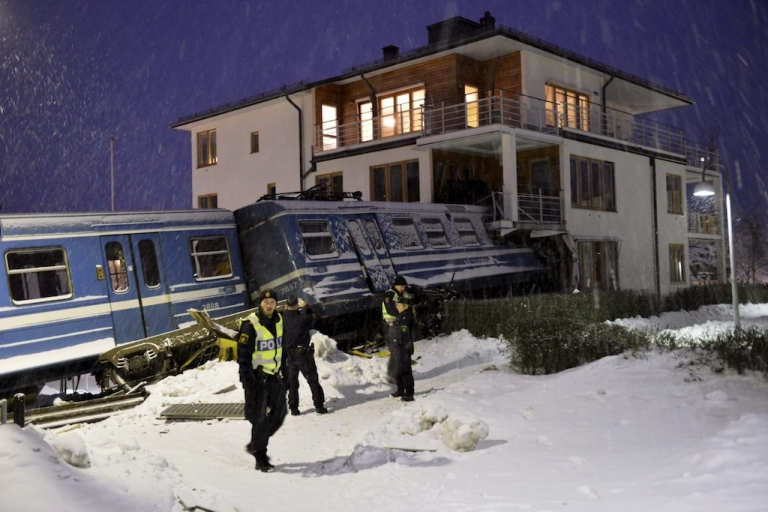 <p>Policemen stand in front of a local train that derailed into a residential building in Saltsjoebaden, Sweden, on January 15, 2013. A domestic cleaner stole the train and drove it into the building and was taken to hospital after the crash.</p>
