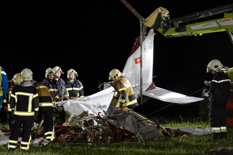 <p>Firemen remove the wreckage of a small plane thatcrashed today in western Switzerland. The aircraft plunged into a field not far from houses in the village. It flew over the town twice before crashing around 3:00 pm local time. The passengers and pilot could not immediately be identified.</p>