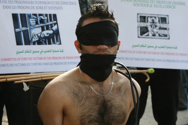 <p>A Syrian protestor mocks being tortured during a sit-in. A new Amnesty International report says at least 88 Syrians have died in detention since uprising began.</p>