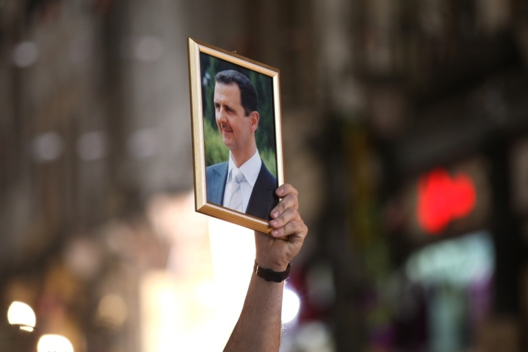 <p>A Syrian man holds up a portrait of President Bashar al-Assad during a rally to show their support for the president in Damascus on April 30, 2011.</p>