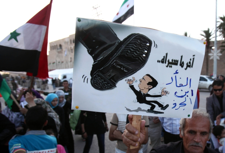 <p>A Syrian man living in Libya holds an anti-Syrian President Bashar al-Assad caricature that reads in Arabic