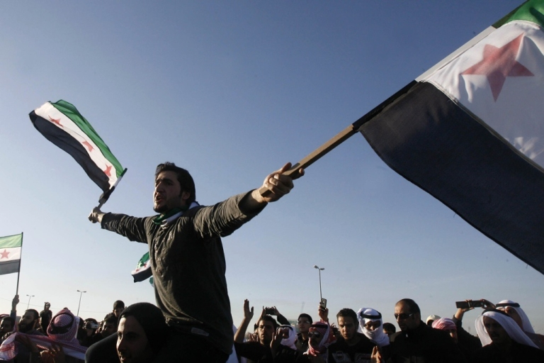 <p>Syrians living in Kuwait wave the pre-Baath Syrian flags outside the Syrian embassy in Kuwait City during a protest against the bloodshed in Syria on Feb. 4, 2012.</p>
