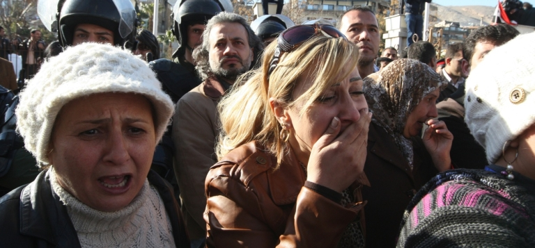 <p>Syrians grieve after bomb blasts in Damascus on March 18, 2012.</p>