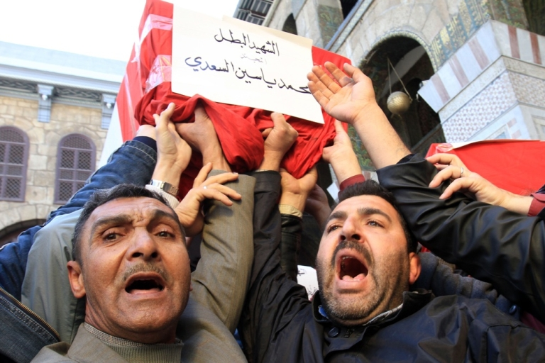 <p>Syrian mourners carry a coffin during the mass funeral of 44 people killed in twin suicide bombings that targeted intelligence agency compounds in Damascus on Dec. 24, 2011.</p>