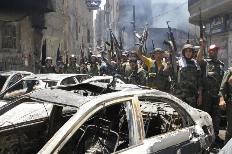 <p>Syrian soldiers celebrate in the Midan area of Damascus on July 20, 2012. Syrian regime forces routed rebel fighters from the Damascus neighborhood, causing many residents to flee for the countryside.</p>