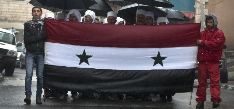 <p>Druze residents of the Golan Heights hold Syrian flags during a rally in the Druze village of Majdal Shams on Feb. 14, 2011 in protest against the 1981 Israeli annexation of the strategic plateau. Israel captured the Golan Heights from Syria after the 1967 Arab-Israeli war.</p>