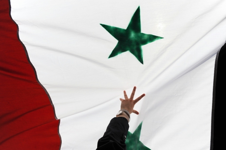 <p>A woman holds up a Syrian flag during a demonstration in Turkey on July 29, 2011.</p>